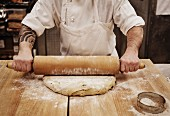 A baker in a bakery rolling out dough with a rolling pin