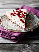 A slice of cheesecake with pomegranate seeds