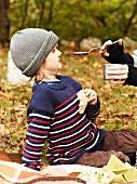 Frau füttert Kind mit Rote-Bete-Suppe beim Herbstpicknick