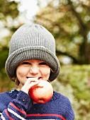 Mädchen hält Apfel beim Herbstpicknick