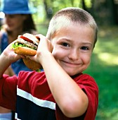 A blond boy with a burger at a picnic in a garden