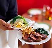A waiter serving beef tenderloin with fries and spinach