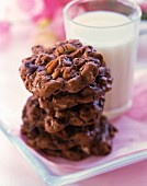 A stack of chocolate and nut cookies and a glass of milk