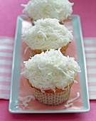 Three cupcakes decorated with vanilla frosting and grated coconut