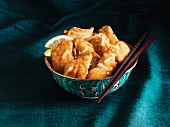 Chinese lemon chicken in a bowl with chopsticks