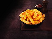 A bowl of thick-cut chips with ketchup and pepper