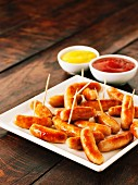 Fried cocktail sausages on sticks on a plate with dishes of ketchup and mustard