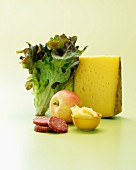 An arrangement of cheese, salami, an apple and an oak leaf