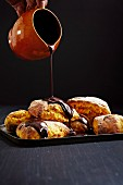 Chocolate sauce being poured over carrot rolls