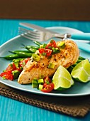 Chicken breast on a bed of green beans with a tomato and avocado salsa