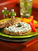 A poppy seed and sesame bagel with herb feta cheese