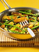 Fried potatoes with green asparagus and mint