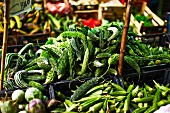 Bitter gourds and okra pods at a market (Italy)