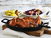 Sweet and sour goose legs with apple red cabbage and salted potatoes