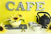 Alte Kaffeekanne, Aluminiumtassen und Sonnenblumen