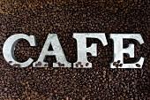 Schriftzug CAFE auf Kaffeebohnen