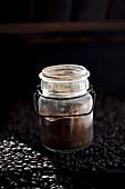 A jar of coffee powder on coffee beans