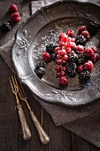 Fresh berries with sugar on a pewter plate