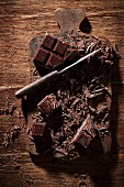 Chopped dark chocolate with a knife on a wooden board