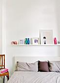 Aneinander gereihte Kissen auf Bett, darüber weiße Ablage mit Bildern und Figuren im Schlafzimmer