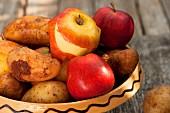 Kartoffeln und Äpfel in einer Keramikschale