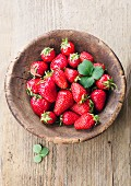 Fresh strawberries with leaves in a wooden bowl