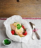 Salmon fillet in parchment paper with lemon and cherry tomatoes