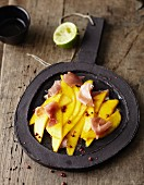 Mango carpaccio with raw ham and hazelnut oil