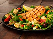 Salmon fillet on a bed of rocket with tomatoes and croutons