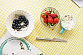 Bowls of blueberries, strawberries and cream cheese on a checked tablecloth