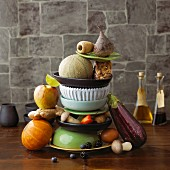 An arrangement featuring a stack of crockery, fruit, vegetables, mushrooms and ginger