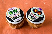 Two Halloween cupcakes decorated with skulls