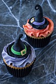 Two Halloween cupcakes decorated with witches hats