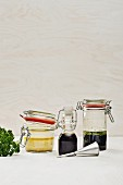 Three different marinades in jars and a bottle
