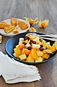 Fruit salad with cranberries and a cheesecake in the background