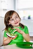 Mädchen mit grünem T-Shirt isst Brot mit Frischkäse und Gurken