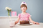 A little girl wearing a crown sitting at a table in front of her birthday cake