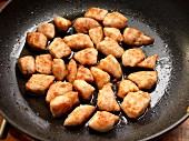 Flour-dusted chicken breast frying in a pan