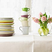 A stack of plates, a stack of cups and a bunch of flowers on a table laid with a white cloth