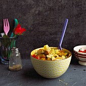 A bowl of rigatoni with courgettes, tomatoes and tofu