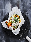 Flounder on root vegetables in parchment paper