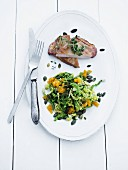 Pork chop with a green kale and orange salad