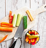 Raw vegetables with a knife on a chopping board
