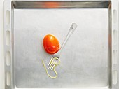 An egg timer and a fork with a strand of spaghetti on a baking tray