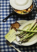 Green asparagus and grilled bread on plates with a sticky note and a saucepan of chicken in the background