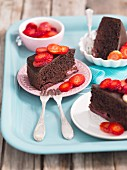 Three slices of chocolate cake with strawberries