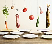 Vegetables, meat, poultry and fish hanging above plates