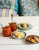 Two jars of jam, rosemary and Parmesan crackers and nut crispbread