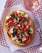 A crostino topped with artichoke hearts, tomatoes, coppa and mozzarella