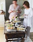 Festliches Buffet mit verschiedenen Häppchen auf rustikalem Holztisch und jungen Frauen mit Tellern